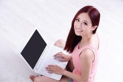 Sonrisa de la mujer usando el ordenador portátil Fotos de archivo libres de regalías