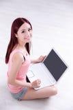 Sonrisa de la mujer usando el ordenador portátil Imágenes de archivo libres de regalías