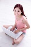 Sonrisa de la mujer usando el ordenador portátil Fotos de archivo