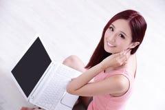 Sonrisa de la mujer usando el ordenador portátil Fotografía de archivo