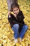 sonrisa de la niña asentada en hojas amarillas Foto de archivo libre de regalías