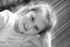Sonrisa de la niña con la piel joven de la cara El ni?o feliz disfruta de d?a soleado Sonrisa del niño de la moda al aire libre V foto de archivo
