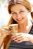 Sonrisa de la taza de café de la explotación agrícola de la mujer joven fotos de archivo