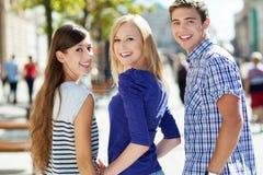 Sonrisa de tres personas jovenes Imagen de archivo