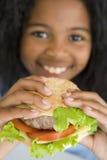 Sonrisa del cheeseburger de la consumición de la chica joven Imagenes de archivo