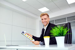 Sonrisa del hombre de negocios rubia para un ordenador portátil en su escritorio en la oficina Fotografía de archivo libre de regalías
