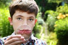 Sonrisa del muchacho del adolescente con la lupa Foto de archivo libre de regalías