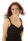 Sonrisa del pelo de la mujer pequeña del soplo del vestido rojo del negro Foto de archivo libre de regalías