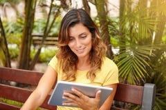 Sonrisa dentuda de la señora joven mientras que usa la tableta Imagen de archivo libre de regalías