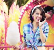 Sonrisa dentuda Mujer joven con el caramelo de algodón en parque de atracciones Imágenes de archivo libres de regalías