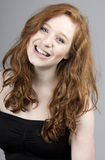 Sonrisa dirigida roja hermosa de la muchacha Fotografía de archivo libre de regalías