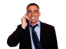 Sonrisa ejecutiva hispánica con un teléfono Imágenes de archivo libres de regalías