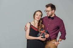 Sonrisa elegante hermosa del hombre y mujer joven hermosa de abarcamiento que sostienen la caja de regalo Imágenes de archivo libres de regalías