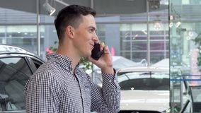 Sonrisa emocionada del hombre, celebrando llaves del coche en la representación, hablando en el teléfono almacen de metraje de vídeo