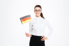 Sonrisa empresaria bastante joven que coloca y que sostiene la bandera de Alemania Fotografía de archivo libre de regalías