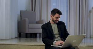 Sonrisa en un buen oficinista del humor que mecanografía algo en su ordenador portátil mientras que lo sienta en casa sea baya  almacen de metraje de vídeo