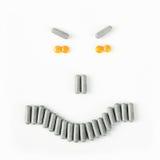Sonrisa enojada hecha de muchas píldoras y cápsulas Concepto de la salud Foto de archivo libre de regalías