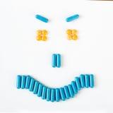 Sonrisa enojada hecha de muchas píldoras y cápsulas Concepto de la salud Fotos de archivo libres de regalías