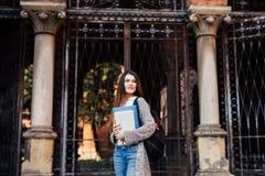 Sonrisa estudiante de mujer bastante joven con la mochila que camina al aire libre cerca de campus Imágenes de archivo libres de regalías