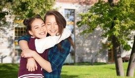 Sonrisa feliz abrazo bastante adolescente de las muchachas del estudiante Foto de archivo libre de regalías