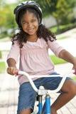 Sonrisa feliz de la bici del montar a caballo de la muchacha del afroamericano Imágenes de archivo libres de regalías