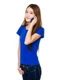 Sonrisa feliz de la chica joven asiática y discurso en el teléfono móvil Imagen de archivo