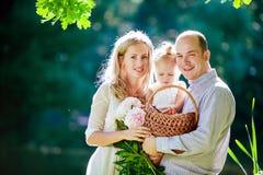 Sonrisa feliz de la mamá, del papá y de la hija en el fondo de las delanteras foto de archivo