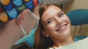 Sonrisa feliz de la muchacha con los apoyos ortodónticos almacen de video