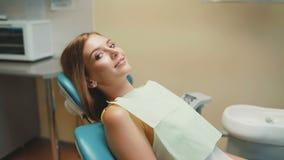 Sonrisa feliz de la muchacha con los apoyos ortodónticos en silla dental 4K metrajes