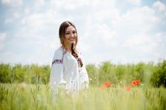 Sonrisa feliz de la muchacha rubia hermosa divirtiéndose que se coloca en campo y que mira la cámara en el cielo azul del verano  Foto de archivo libre de regalías