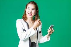 Sonrisa feliz de la muchacha tailandesa con el teléfono móvil Fotos de archivo
