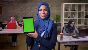 Sonrisa feliz de la mujer árabe que está mostrando la pantalla verde en su tableta y se está colocando en oficina moderna, mujere almacen de video
