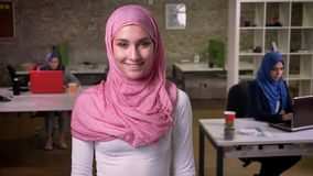 Sonrisa feliz de la mujer árabe que se coloca tranquilamente cerca de otras muchachas musulmanes, hijab que lleva, diversidad col metrajes