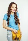 Sonrisa feliz de la mujer bastante larga del pelo de los jóvenes aislada en el fondo blanco, bolso minúsculo lindo que lleva, gen Imagen de archivo libre de regalías
