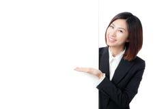 Sonrisa feliz de la mujer de negocios que muestra la cartelera en blanco Fotografía de archivo libre de regalías