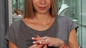 Sonrisa feliz de la mujer, intentando en el anillo de diamante en venta en los joyeros metrajes