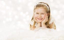 Sonrisa feliz de la niña, mintiendo abajo manos debajo de mejillas blanco Fotografía de archivo