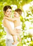 Sonrisa feliz del bebé de la madre Niño en mamá de abarcamiento del pañal sobre g Imagenes de archivo