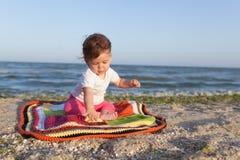 Sonrisa feliz del bebé y mano que agita, sentándose en la playa tropical arenosa blanca en la alfombra fotografía de archivo