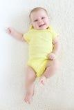 Sonrisa feliz 2 meses de bebé en mono amarillo Fotos de archivo libres de regalías