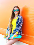Sonrisa feliz muchacha bastante rubia llevando las gafas de sol con el monopatín que se divierte Imagenes de archivo