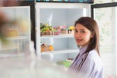 Sonrisa femenina asiática atractiva delante del refrigerador abierto en la torta imagen de archivo libre de regalías