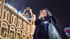 Sonrisa femenina joven de moda con el bolso de compras de la Navidad en el fondo de iluminación de las luces almacen de video