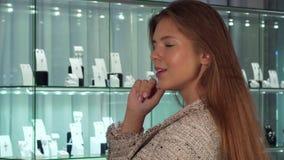 Sonrisa femenina joven del cliente, eligiendo las joyas en venta en la tienda de lujo almacen de metraje de vídeo