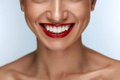 Sonrisa hermosa con los dientes blancos sanos y los labios rojos Fotos de archivo