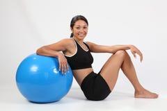 Sonrisa hermosa de la bola del ejercicio de la mujer joven del ajuste Imagen de archivo libre de regalías