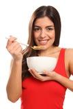 Sonrisa hermosa de la chica joven que come el cereal de desayuno Fotos de archivo