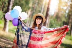 Sonrisa hermosa de la mujer del patriota con la bandera americana y los globos coloridos foto de archivo libre de regalías