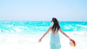 Sonrisa hermosa de la mujer feliz el vacaciones de verano en la playa blanca Muchacha feliz que camina en vestido del verano metrajes