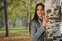 Sonrisa hermosa de la mujer, inclinada en un árbol de abedul Imágenes de archivo libres de regalías